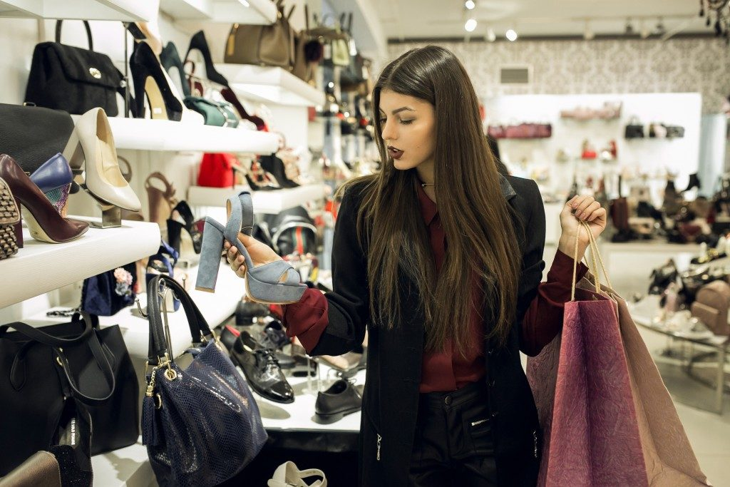 fashionable woman looking for bag and shoes
