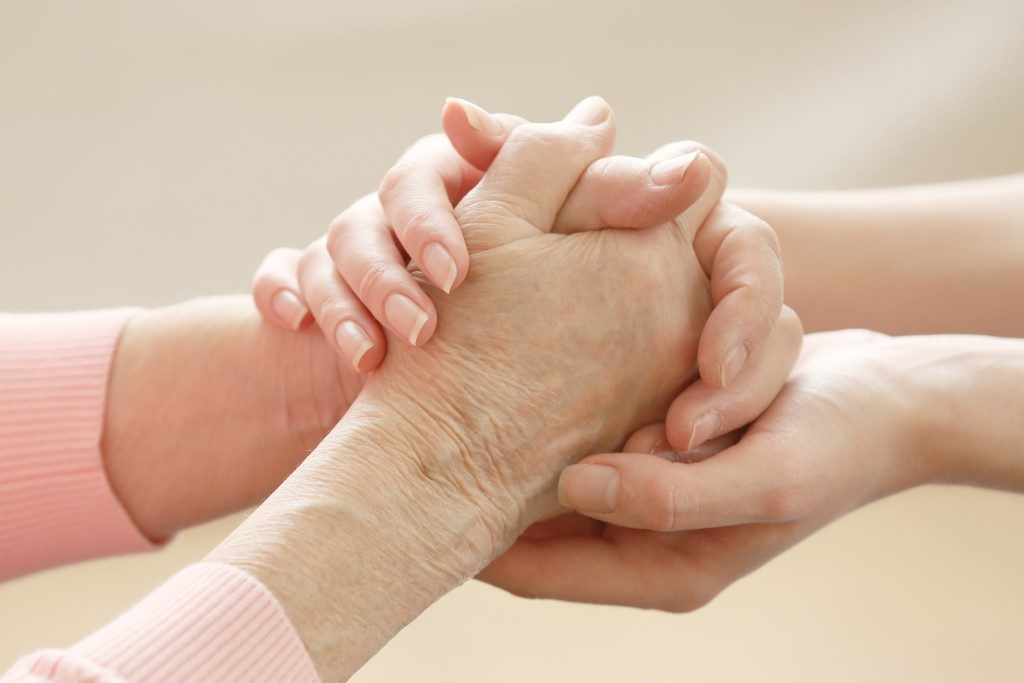 person offering support to elderly
