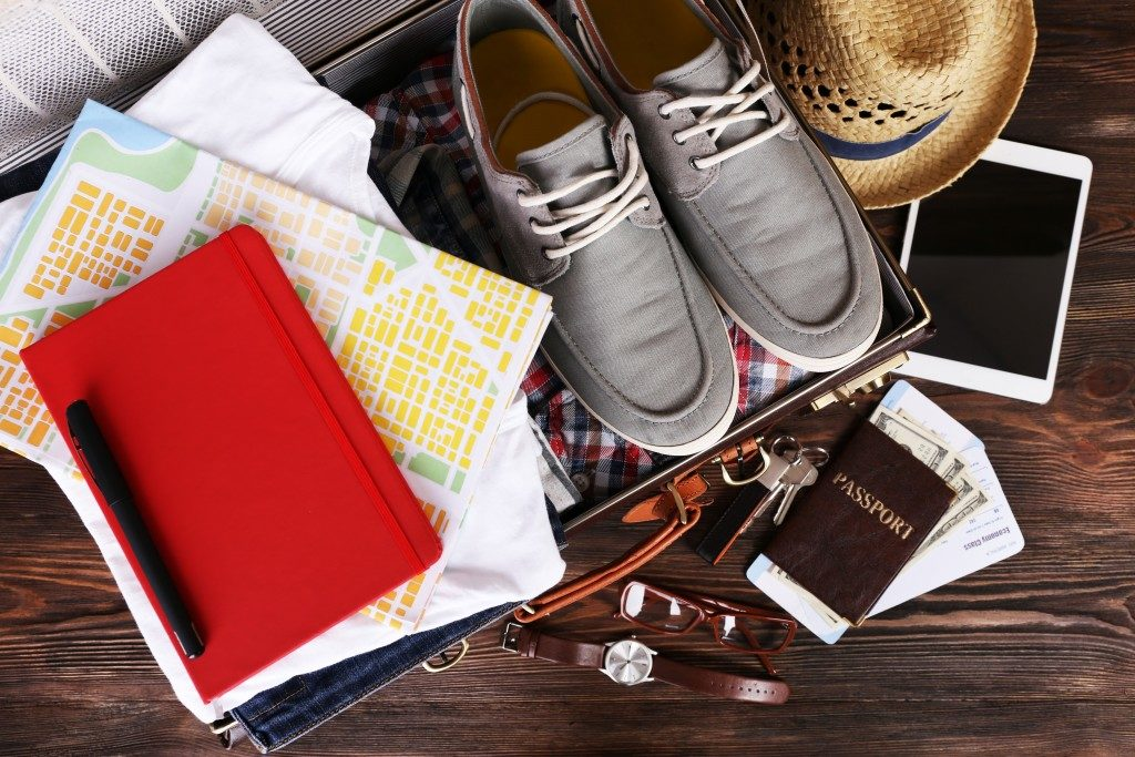 Packed suitcase of vacation items on wooden table