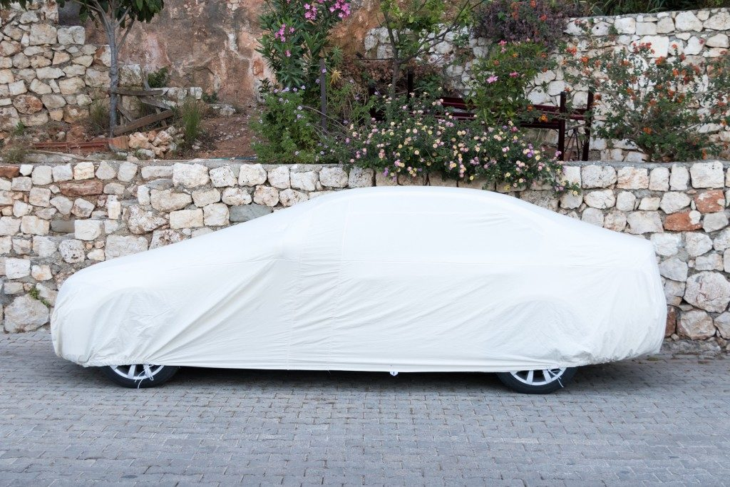Car covered with white sheet on the pavement