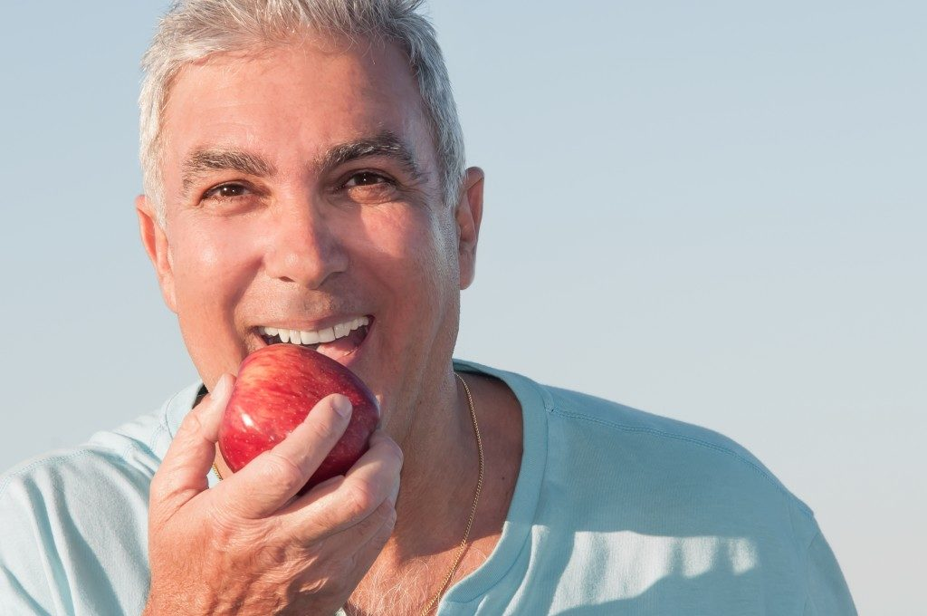man eating an apple outdoors