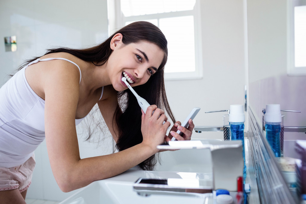 Female using an electric toothbrush