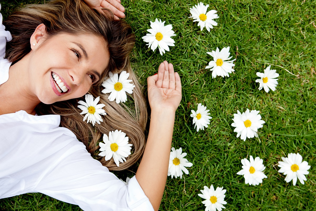 happy woman on the grass with scattered flowers