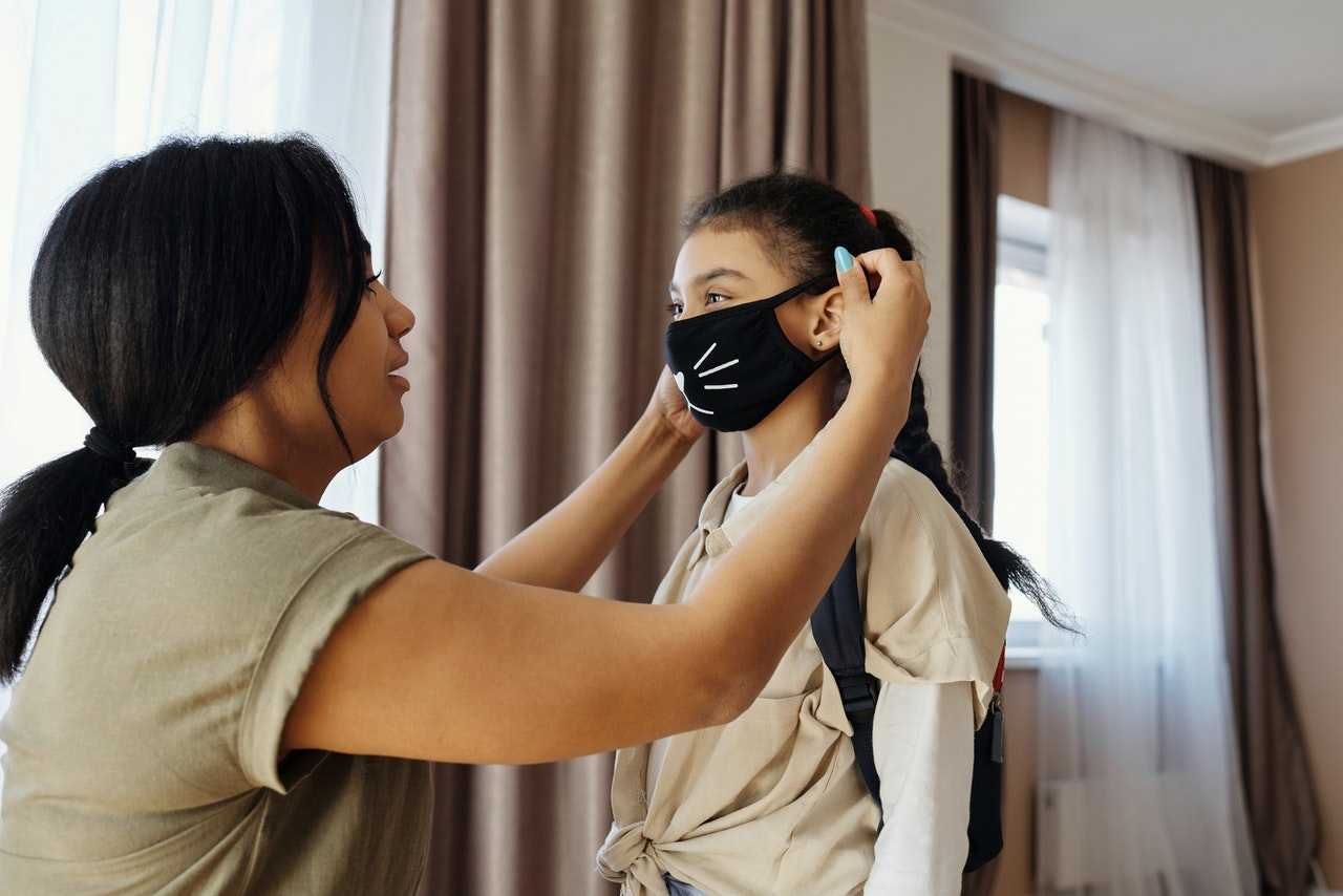 putting facemask on young girl