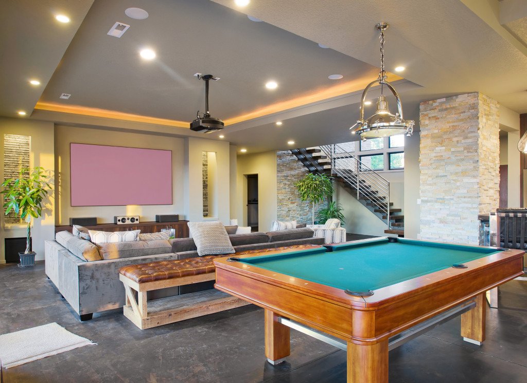 a billiard table, sofa, and a big television inside a house space